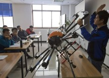 In this Oct. 17, 2015 photo, an instructor explains the operation of a drone to students at a school run by TT Aviation Technology in Beijing. TT Aviation Technology Co. - and their instructors - are part of a cottage industry sprouting up in China, where drones are being deployed in rising numbers and touted as a game-changer in agriculture, logistics, film production and law enforcement. (AP Photo/Ng Han Guan)
